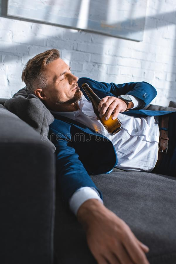 betrunkener Geschäftsmann, der auf Sofa und trinkendem Alkohol liegt stockfotos