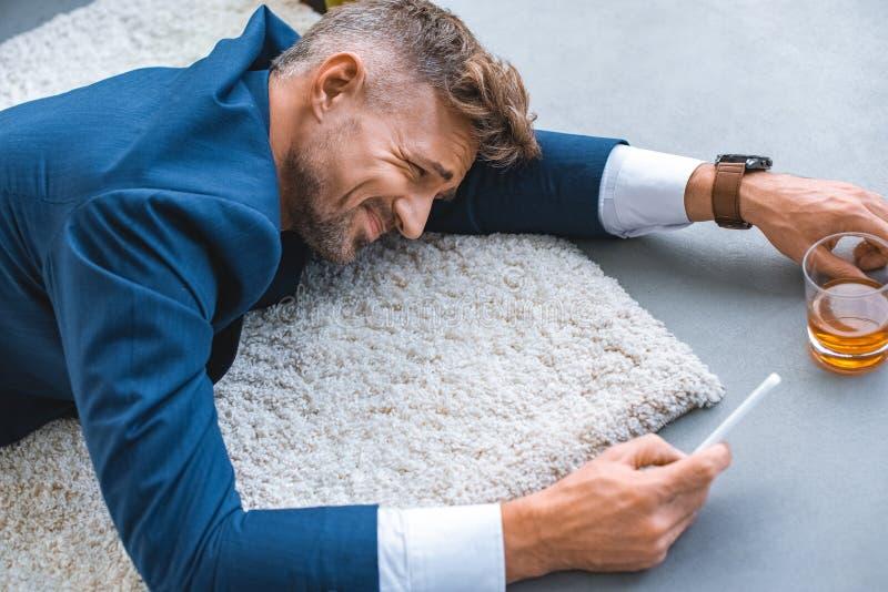 betrunkener Geschäftsmann, der auf Teppich mit Smartphone liegt stockbilder