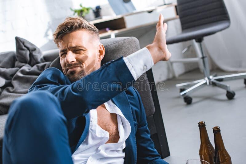 betrunkener Geschäftsmann, der herein Hand gegen Sonnenschein setzt stockfotografie