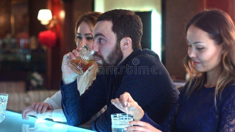 Betrunkener, müder Geschäftsmann, der am Zähler in der Bar mit zwei jungen Frauen sitzt lizenzfreies stockbild