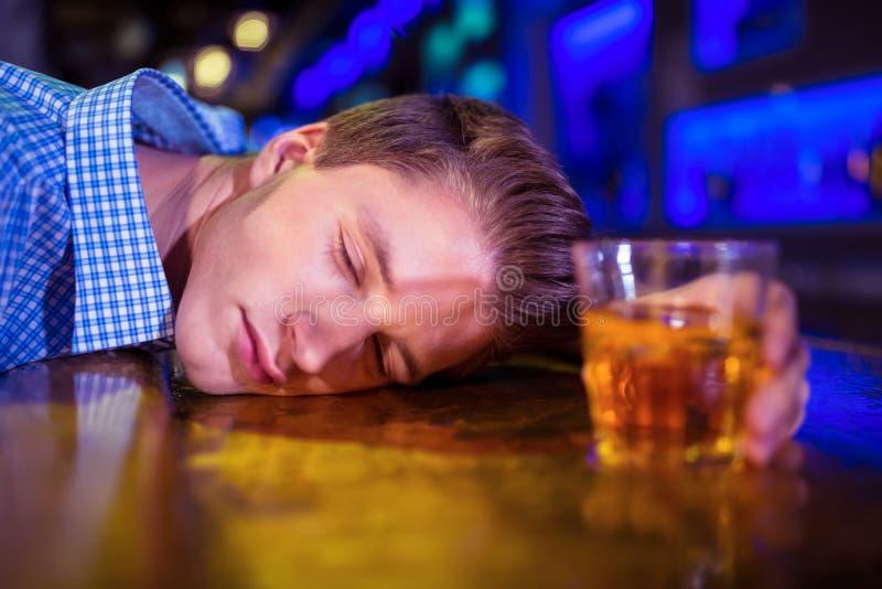 Betrunkener Mann, der auf Barzähler liegt stockfoto