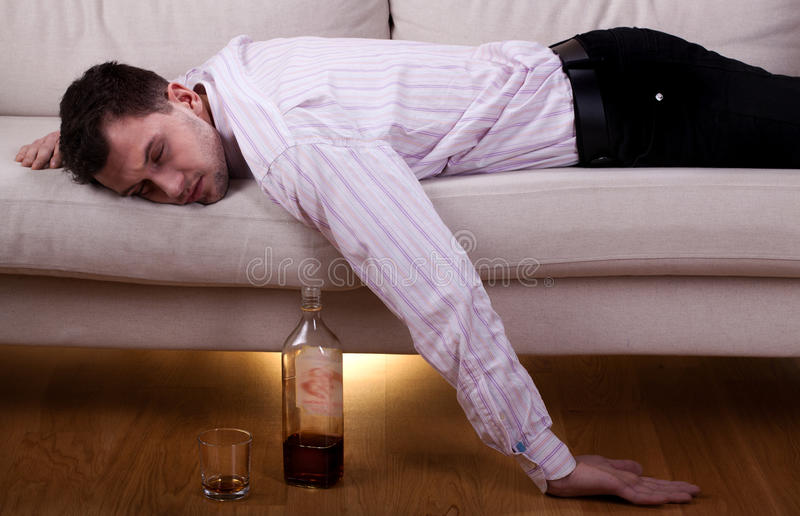 Betrunkener Mann, der auf dem Sofa schläft lizenzfreie stockbilder