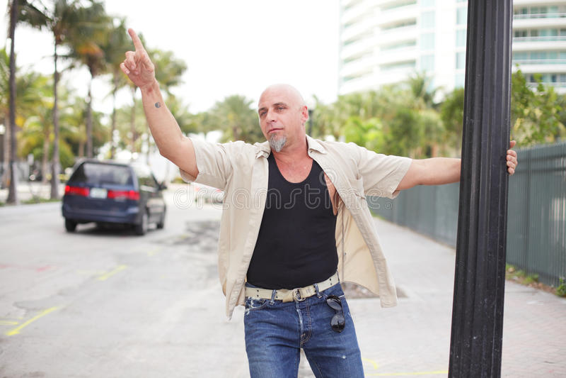 Betrunkener Mann, der von einem Pol hängt lizenzfreies stockfoto