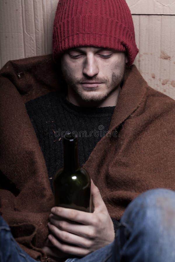 Betrunkener obdachloser Mann mit einer Flasche Wein stockfotografie