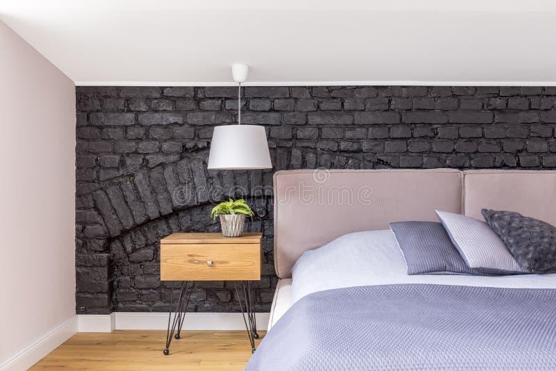 Bett gegen schwarze Backsteinmauer lizenzfreies stockfoto