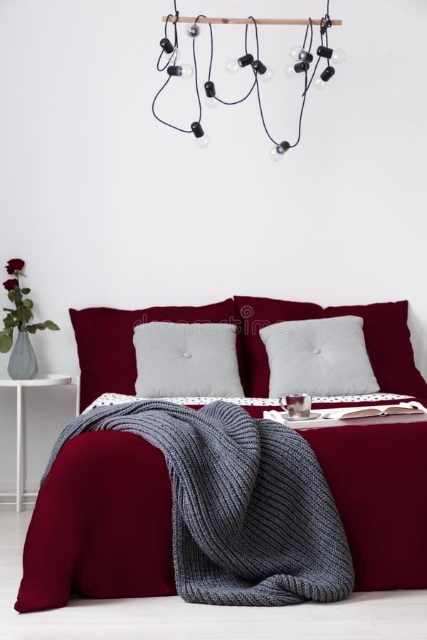 Bett kleidete in den Rotweinkissen und -abdeckung in einem einfachen Schlafzimmerinnenraum an Reales Foto stockfoto