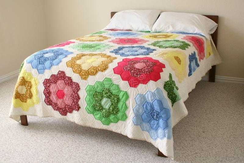 Bett mit Blumensteppdecke stockfoto