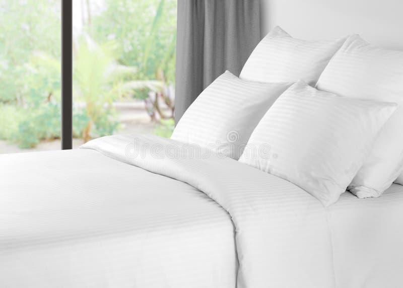 Bett mit Leinen gegen ein Fenster mit grauen Vorhängen stockfotos