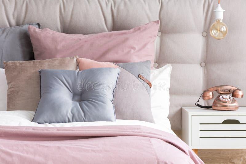 Bett mit Pastellfarbkissen stockbild