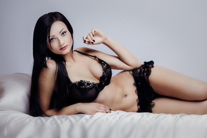 Bett sexy Brunette lizenzfreie stockfotografie