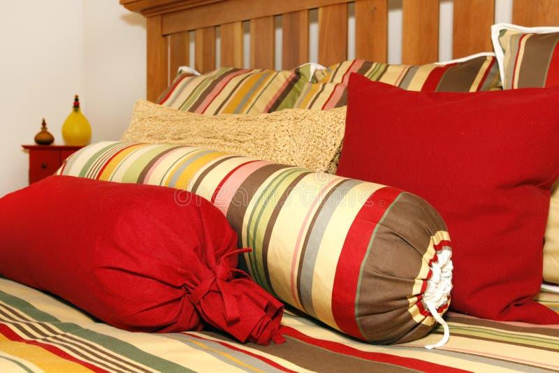 Bett und Kissen in den roten, gelben und grünen Streifen. lizenzfreie stockfotografie