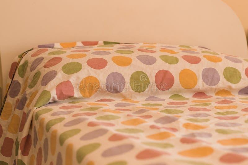 Bett und Kissen mit farbigen pois stockbilder