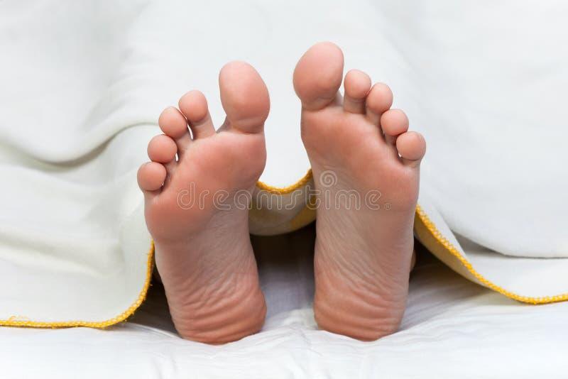 Bettdecke auf menschlichem Fuß stockbild