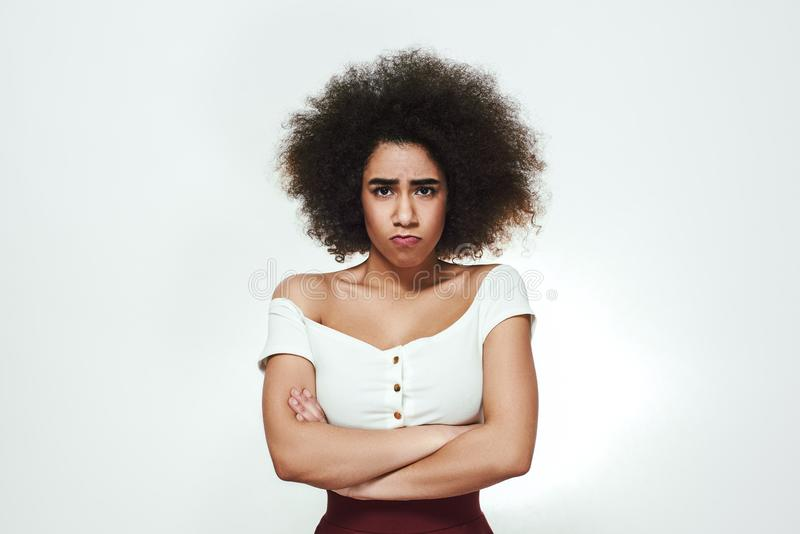 Better not to touch me! Bored young afro American woman keeping arms crossed and making sad face while standing against stock photo