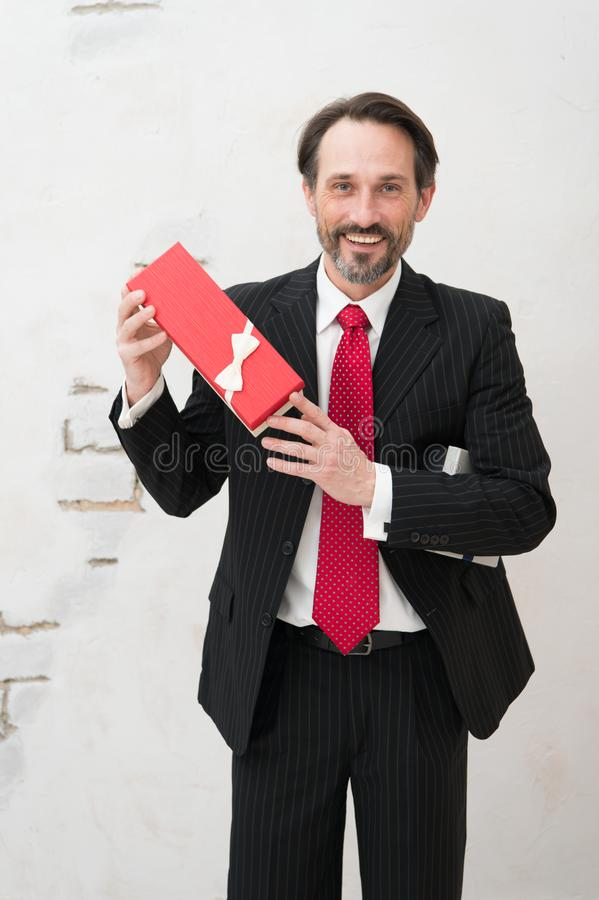Lighthearted charismatic businessman holding a present in red box. Better this one. Cheerful handsome bearded man standing in front of camera and holding a gift royalty free stock image