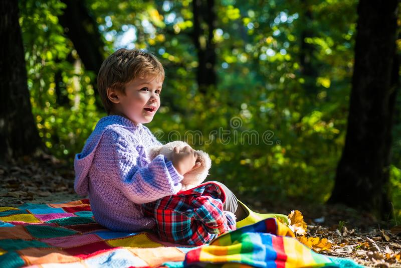 Better together. Happy childhood. Inseparable with toy. Boy cute child play with teddy bear toy forest background. Child stock photography