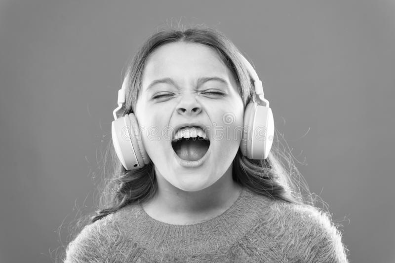 For better vocal performances. Adorable small child doing vocal on song. Little girl listening to music and singing stock photos
