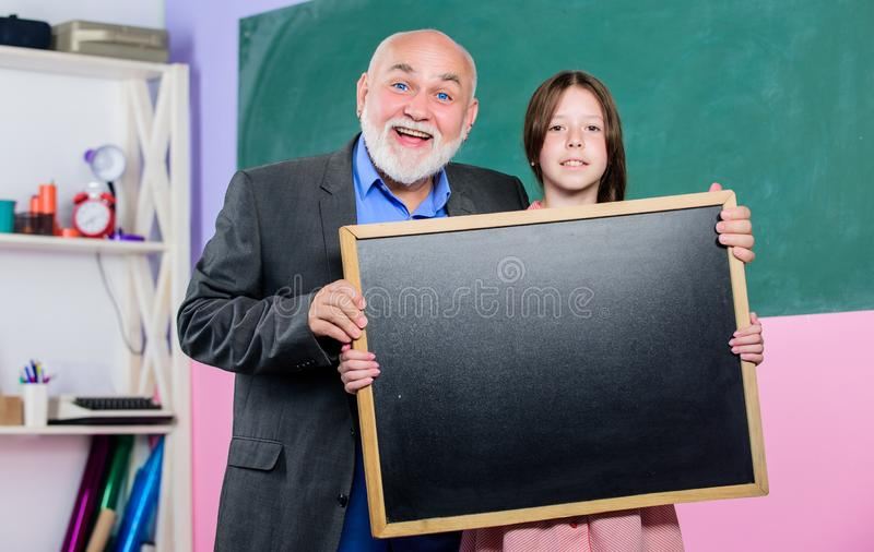 A Better Way Found. mature teacher and happy pupil girl. small girl with man tutor study. blackboard for information and royalty free stock photo