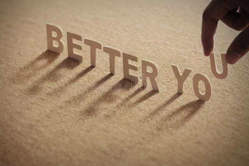 BETTER YOU wood word on compressed board. With human`s finger at U letter stock image