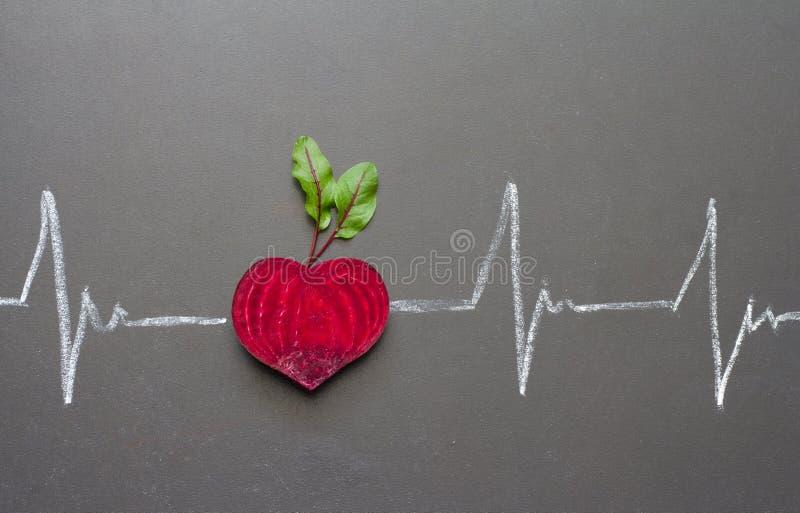 Betteraves saines avec la forme de coeur et électrocardiogramme sur le tableau noir photographie stock
