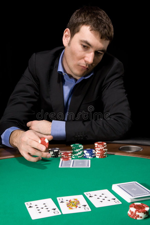 Betting in casino. Stylish man in doubt before making bet in the casino stock photos