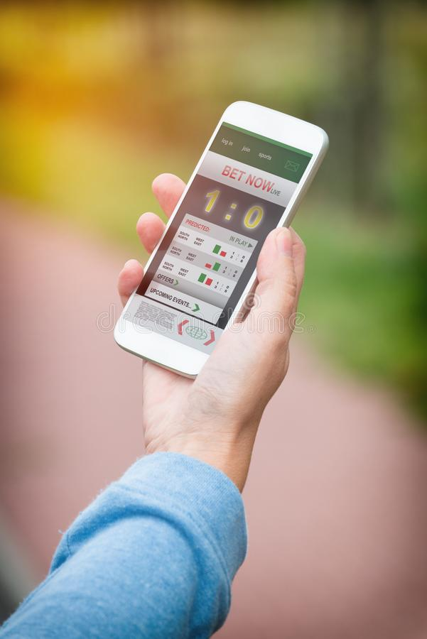 Betting on sports with smartphone stock photography