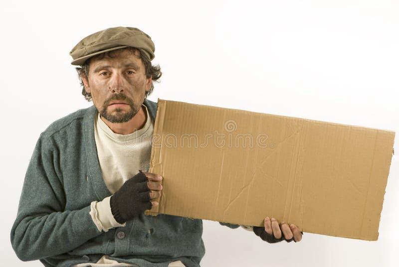 Bettler mit Pappe und Barett lizenzfreie stockfotografie