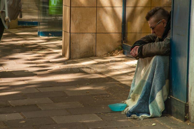 Bettlermann auf der Straße bitten um Geld bettler Lokalisiert auf Wei? Sozialfrage lizenzfreie stockfotografie