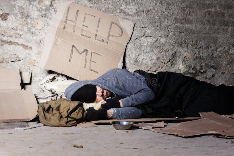 Bettlermann in der alten Kleidung schlafend auf der Straße stockfotografie