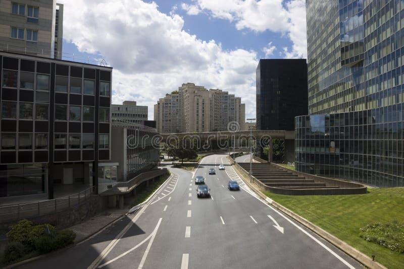betwecarsbyggnader som kör ner en-kontorsgatan royaltyfri fotografi
