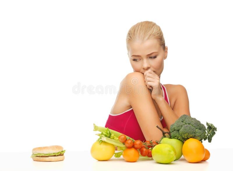 Betwijfelende vrouw met vruchten en hamburger stock afbeeldingen