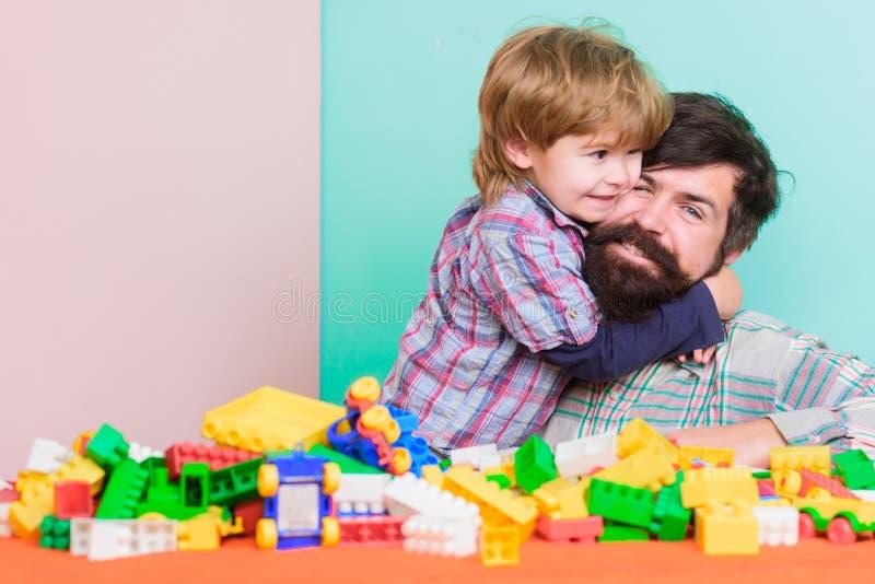 Betydelse av att spela tillsammans Barnav?rdbegrepp lycklig familj Barns utveckling och uppfostran Fadern och sonen har royaltyfri foto