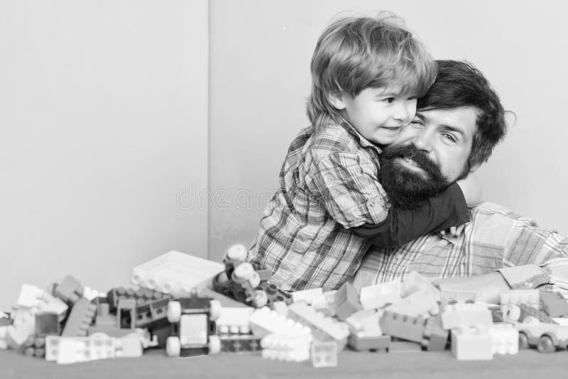 Betydelse av att spela tillsammans Barnav?rdbegrepp lycklig familj Barns utveckling och uppfostran Fadern och sonen har royaltyfria foton