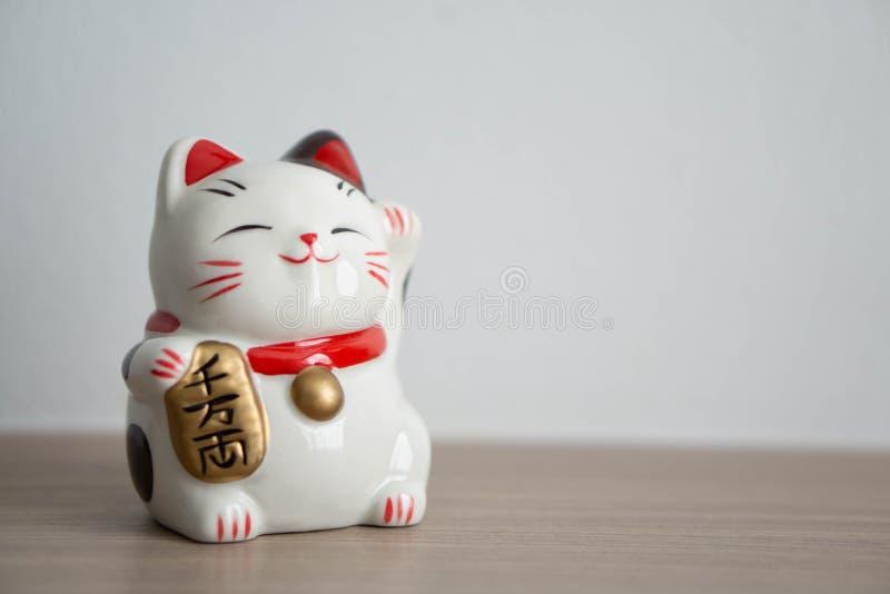 Betydelse för text för show för katt för Maneki neko som lycklig förestående är rik på trätabellbakgrund, vald fokus royaltyfri foto