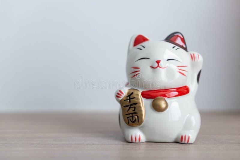 Betydelse för text för show för katt för Maneki neko som lycklig förestående är rik på trätabellbakgrund, vald fokus arkivbilder