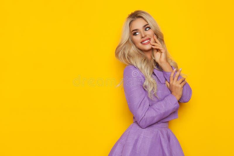 Beuatiful Blonde Vrouw in Violet Costume Is Smiling And die Gele Exemplaarruimte bekijken royalty-vrije stock fotografie