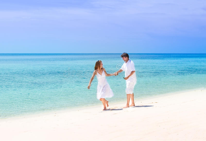 Beuatiful couple running on a tropical beach stock photography