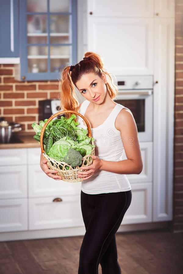 Beuatiful girl holding basket of fresh vegetables on modern scandinavian style kitchen background stock image