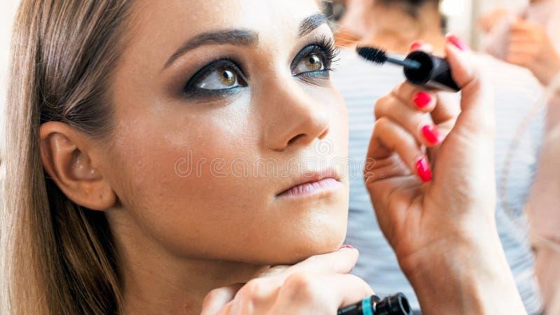 beuatiufl年轻模型特写镜头画象坐在美容院的,当她的被绘时的眼睛 免版税库存图片