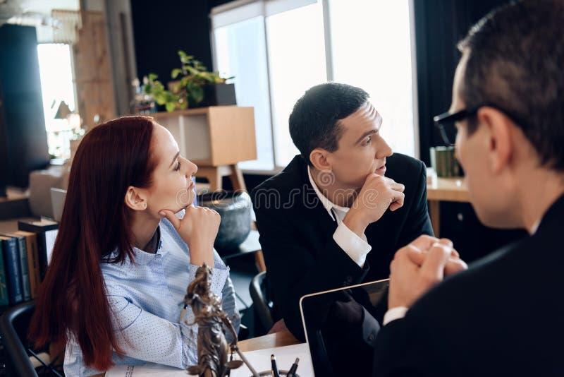 Beunruhigter Ehemann sitzt mit junger Frau hinter Scheidungsanwalt ` s Tabelle stockfoto
