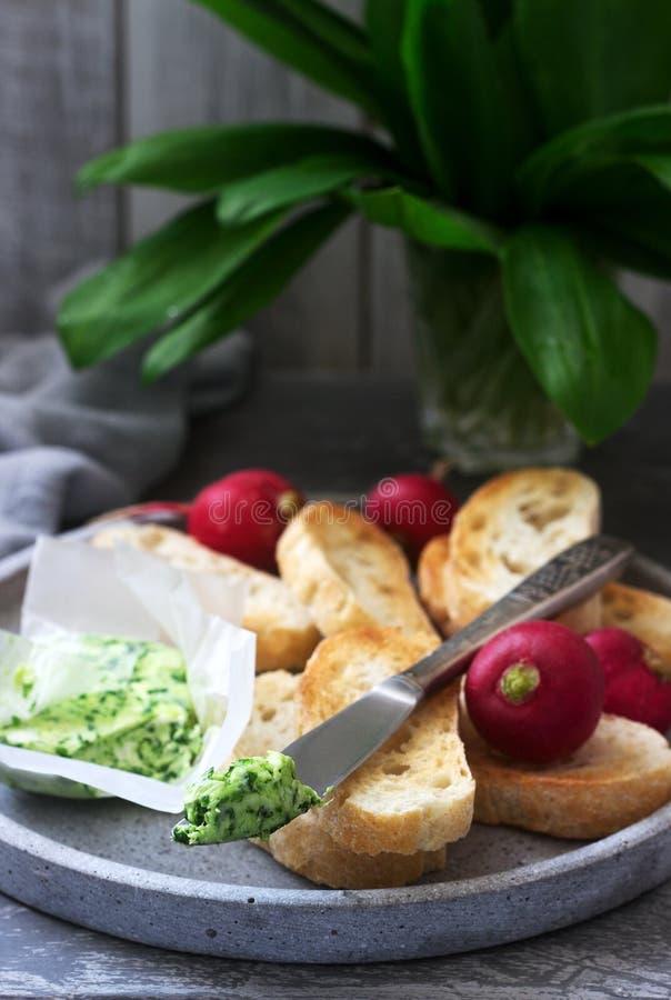 Beurre avec l'ail sauvage, tranches de pain et radis, ingrédients pour faire un sandwich images stock