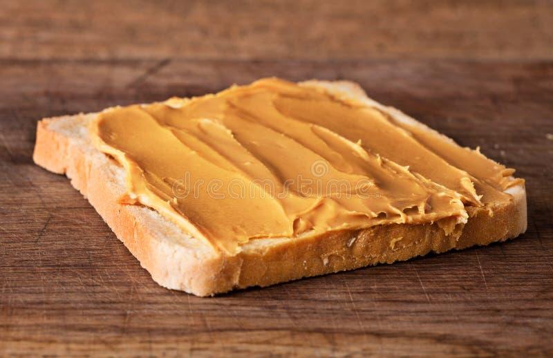 Beurre d'arachide sur le pain grillé photographie stock