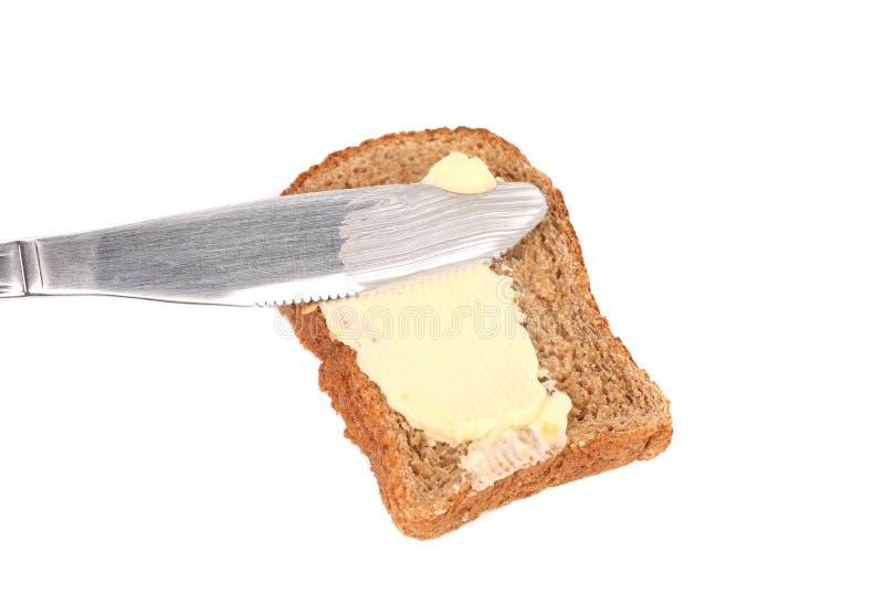 Beurre de calomnie sur le pain le couteau. photos stock
