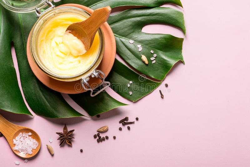 Beurre de ghee dans un pot en verre, un sel rose et des épices sur le fond rose photographie stock libre de droits