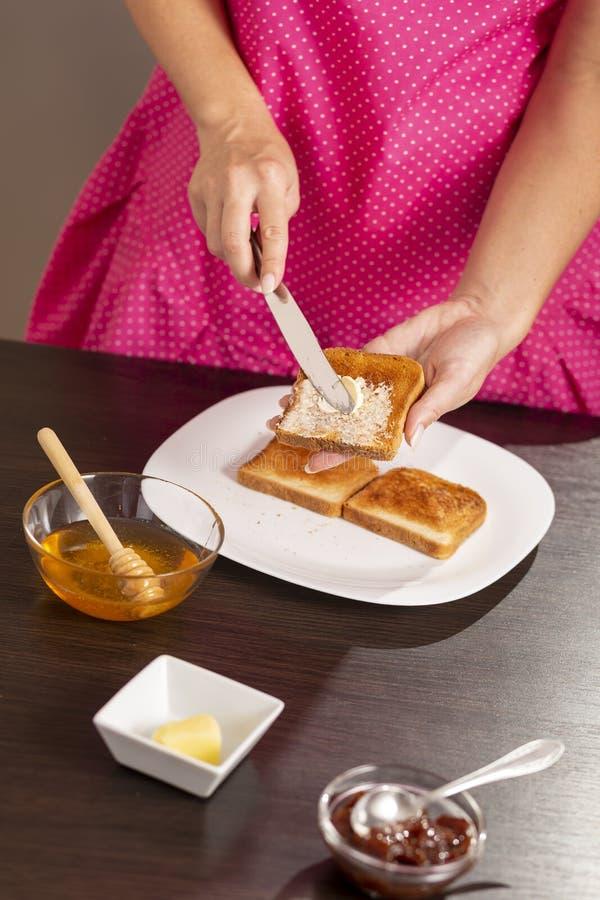 Beurre de propagation au-dessus de pain grillé photos stock