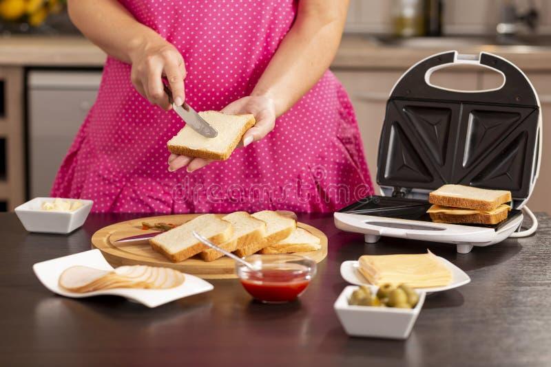 Beurre de propagation de femme au-dessus de tranche de pain photo stock