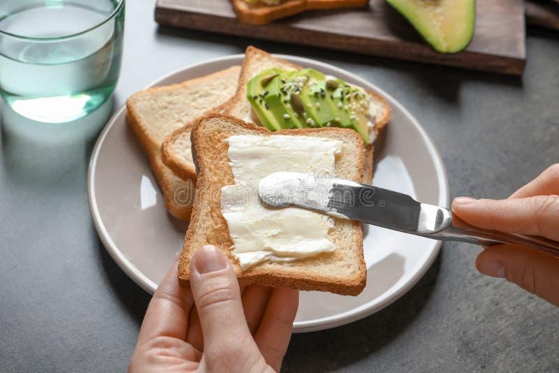Beurre de propagation de femme sur le pain grillé photo stock