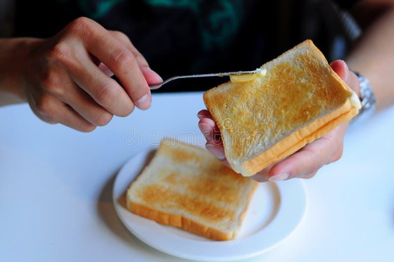 Beurre de propagation sur le pain grillé photo stock
