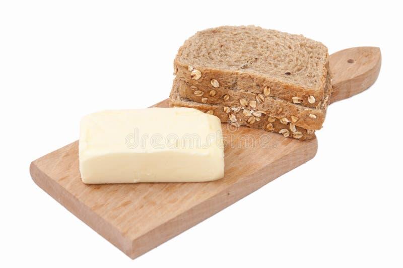 Beurre sain de céréales de pain sur le conseil images stock