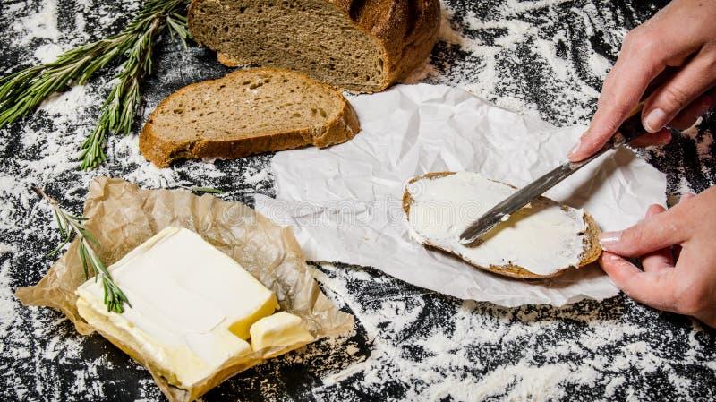 Beurrer du pain avec du beurre photographie stock